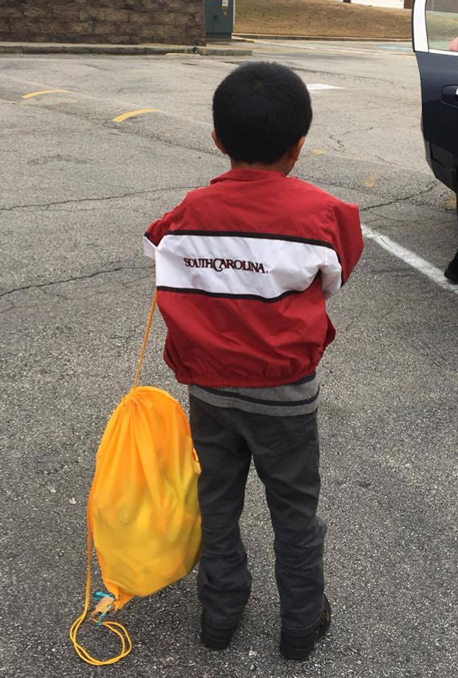 Rear view of a young boy in a parking lot with a jacket that says South Carolina on the back, holding a yellow duffel bag
