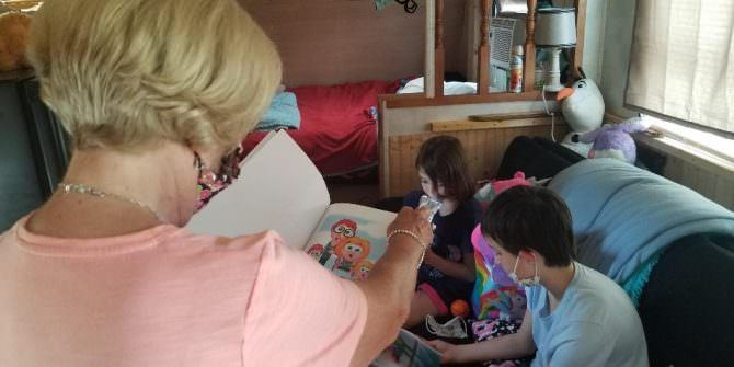 A woman pages through a children's book while several children on a couch look at books as well.