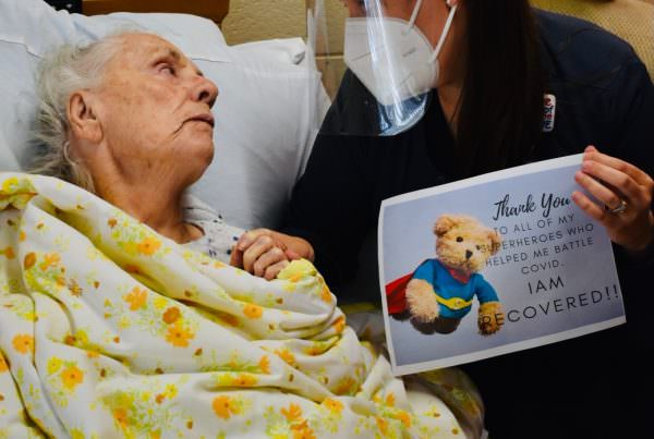 Masked direct care worker looks tenderly at a nursing home resident while holding a sign that celebrates her recovery from COVID