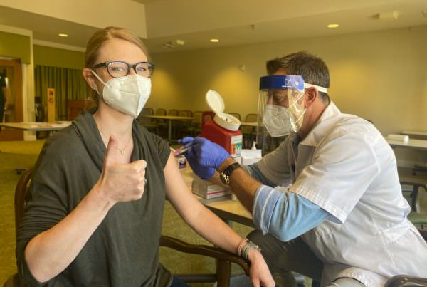 Trinity Grove staff member giving a thumbs up as she gets her COVID-19 vaccination