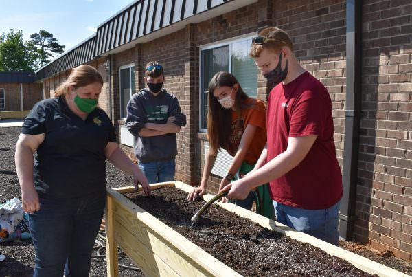 Agriculture teacher and students water the plants in the raised beds.