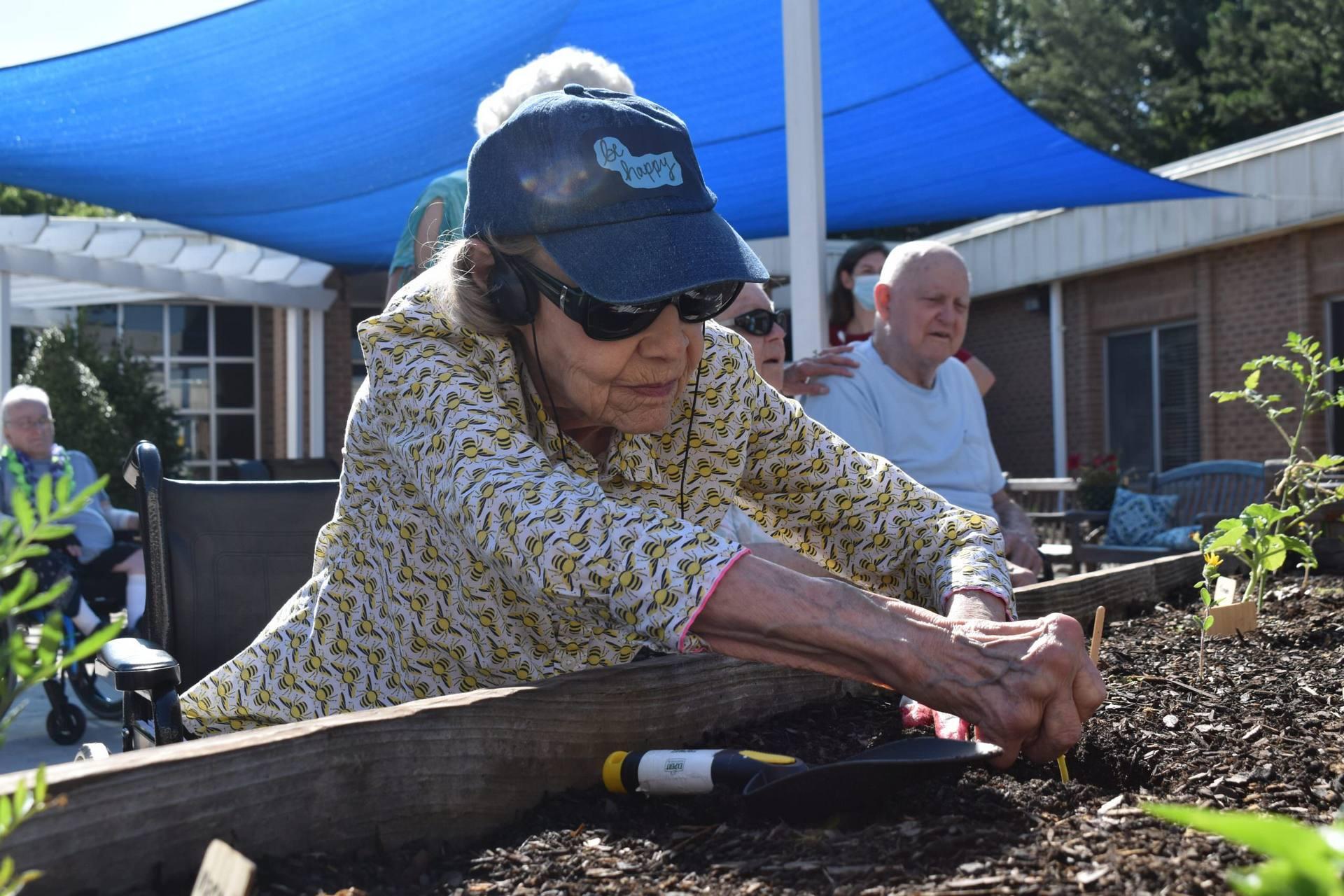 Woman works in courtyard garden.